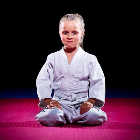karate female: Little girl aikido fighter on black