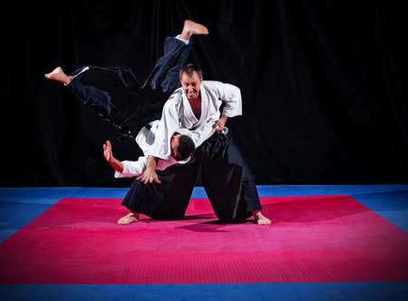 arts: Fight between two aikido fighters on black
