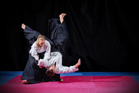 asian art: Fight between two aikido fighters on black