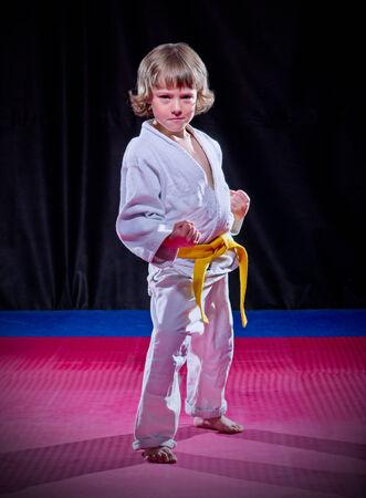 Little boy aikido fighter on black photo