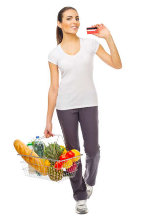 Young girl with food basket and credit card isolated photo