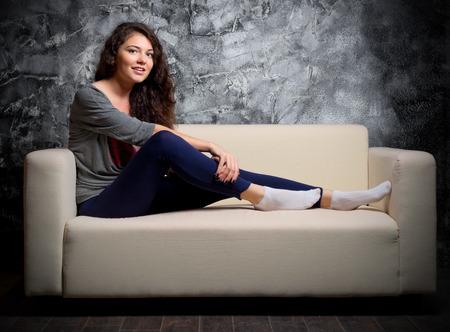 Young girl on sofa at dark room photo