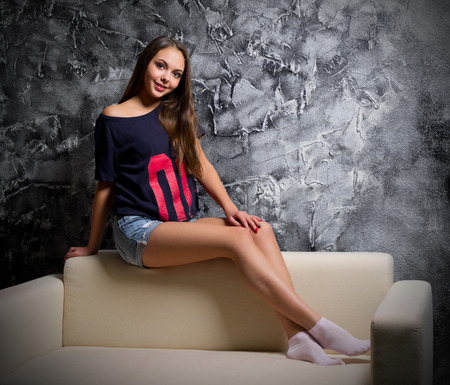 sit: Young girl sit on sofa at dark room Stock Photo