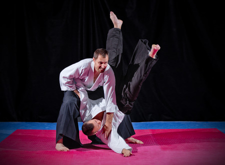 Two martial arts fighters on black photo