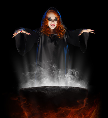 Young witch with cauldron isolated Foto de archivo