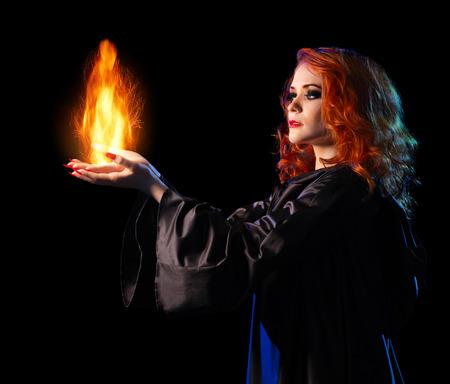 bruja: Chica bruja joven sostiene el fuego aislado en negro