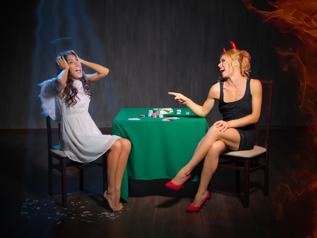 Angel and devil playing cards at room photo