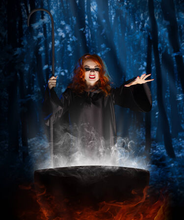 Young witch with cauldron at night forest Stock Photo