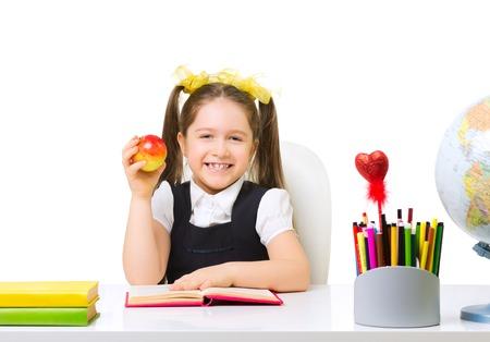 schoolgirl uniform: Schoolgirl at the table isolated