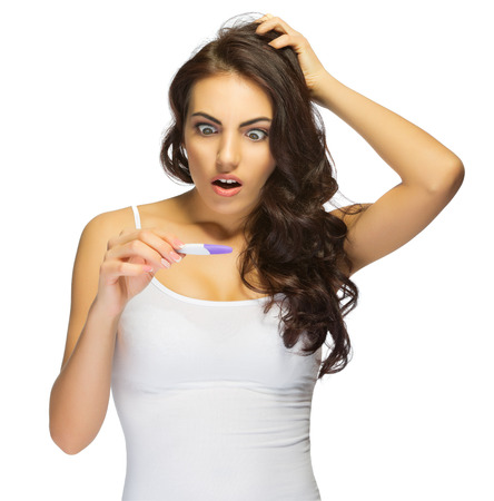 Young surprised girl with pregnancy test isolated photo