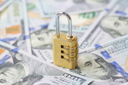 safety lock: Yellow closed padlock and dollars (DOF shallow)