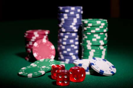 fichas casino: Gambling chips y dados sobre la mesa verde Foto de archivo