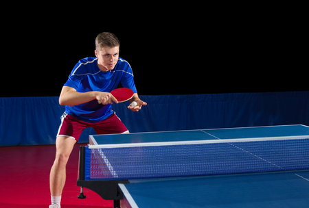 Table tennis player isolated on black Imagens