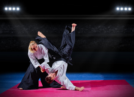 martial arts woman: Fight between two martial arts fighters at sports hall Stock Photo