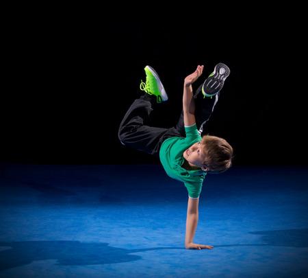 hip hop dance pose: Little boy breakdancer on black Stock Photo