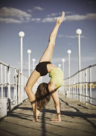 girl sport: Young girl doing gymnastic exercises on the pier (ancient version) Stock Photo
