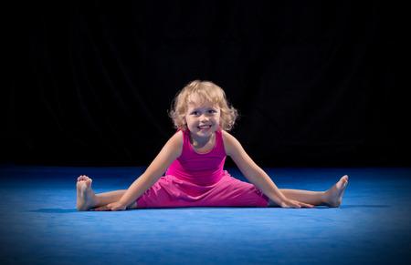 gymnastique: Petite fille de faire des exercices de gymnastique sur le noir Banque d'images
