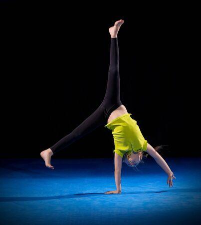 gymnastik: Kleines Mädchen tun Gymnastik-Übungen auf schwarz Lizenzfreie Bilder