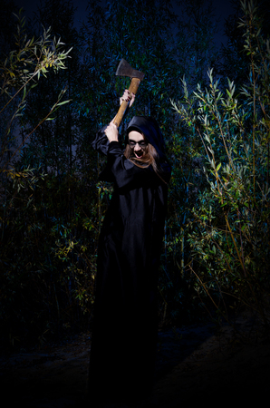 arboles secos: chica del zombi con el hacha en el bosque de la noche
