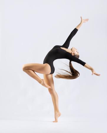 gimnasia: Chica joven que dedica el arte de gimnasia en gris Foto de archivo