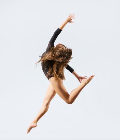 gymnastik: Junges Mädchen engagiert Kunstturn auf grauem