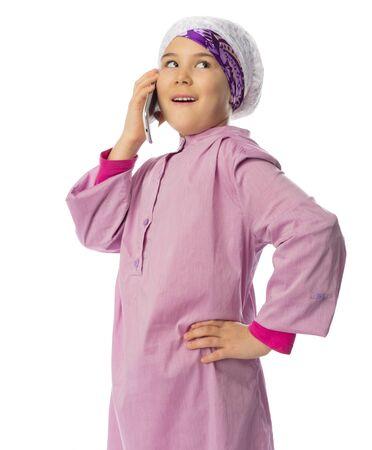 petite fille musulmane: Petite fille dans des vêtements traditionnels musulmans avec les téléphones mobiles isolés