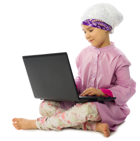 petite fille musulmane: Petite fille musulmane avec un ordinateur portable isolé