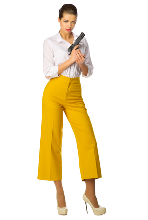 Young girl in yellow pants with gun isolated