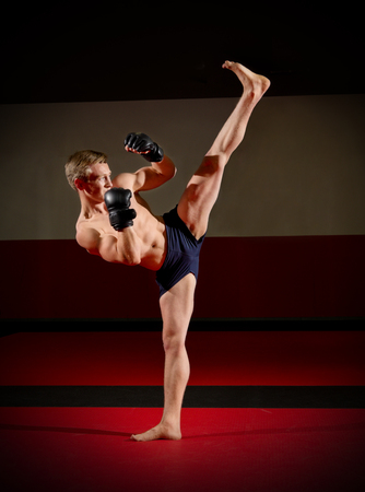Young kickboxer in sports hall