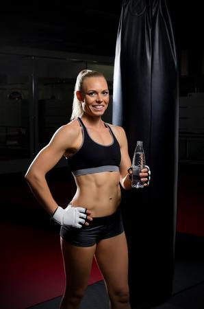 kickboxer: Kickboxer woman with water bottle at gym Stock Photo