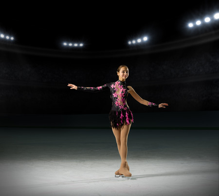 ice arena: Young girl figure skater (on ice arena with spotlights ver)