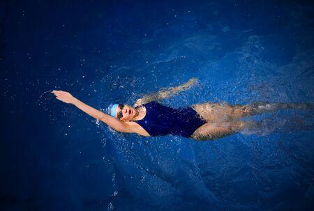 backstroke: Young woman swimmer in blue pool water