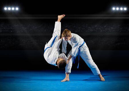 rostrum: Children martial arts fighters in sports hall