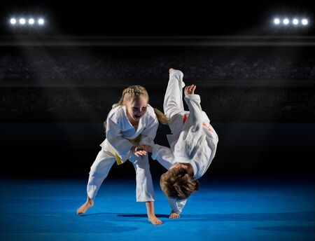 Children martial arts fighters in sports hall