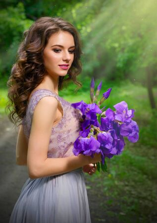 Young woman with flowers in the forest (with sunrays ver) Stock Photo