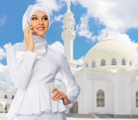 Young muslim girl on white mosque background 免版税图像