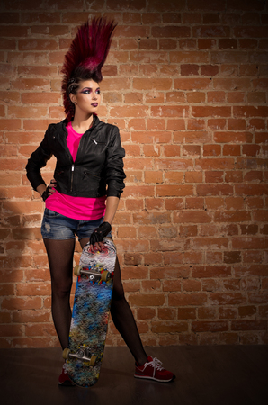 Young punk girl on brick wall background