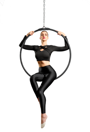 Young woman doing gymnastic exercises on the ring isolated