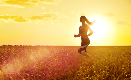 Young sporty woman at sunset in wheat field Stock Photo