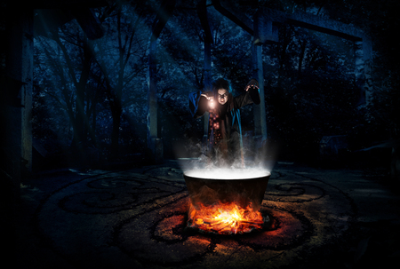 Scary witch in night forest with potion version Stock Photo