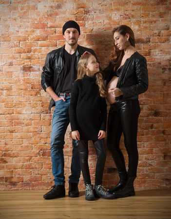 Family in leather clothes on brick wall background (normal version) 免版税图像