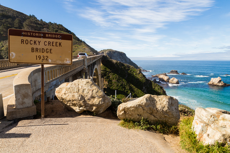 Historic Rocky Creek (Bixby Creek) bridge with sign and view of ocean from the Pacific Coast highway in California