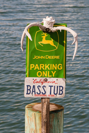 SAN FRANCISCO, CALIFORNIA - March 4, 2018 - John Deere Parking Only sign with deer antlers and bass boat license plate in San Francisco, California.