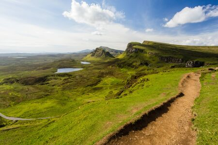 Stunning Quiraing trail view over green cliffs, lochs, trail Isle of Skye Scotland