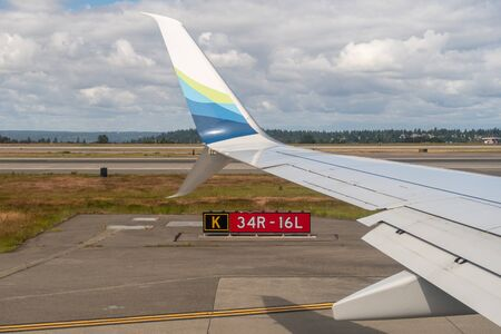 Seattle, Washington - June 6, 2019: Alaska Airlines airplane wing with taxiway markings from passenger seat window view Редакционное