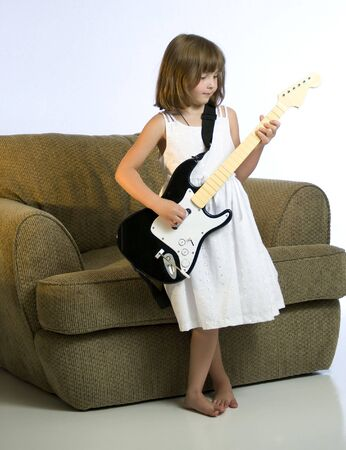 girl playing guitar: Little girl playing video game with a guitar Stock Photo