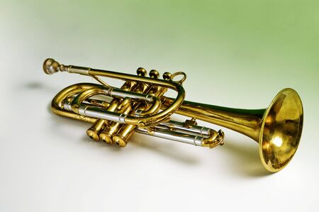 A trumpet containing green reflections in the brass