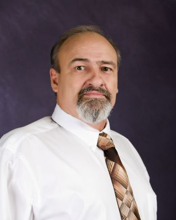 Headshot of business man in white shirt and tie.