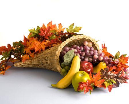 cuerno de la abundancia: A cornucopia de mimbre llena de frutas y hojas de oto�o Foto de archivo