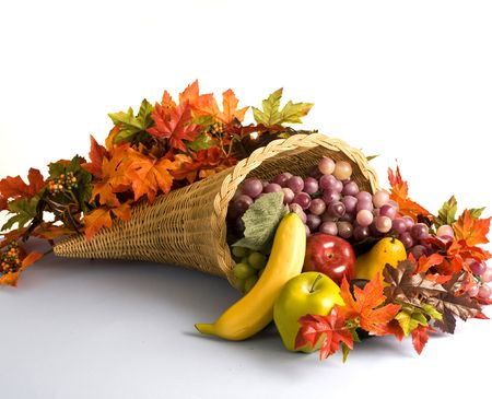 A wicker cornucopia filled with fruits and autumn leaves Stock Photo